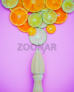 Mixed fresh citrus fruits and wooden juicer for summer citrus juice. Citrus fruits sliced lime,orange and lemon on light pink background flat lay.