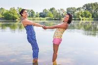 Two women standing together in water