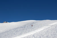 Snowboarder downhill on snowy slope