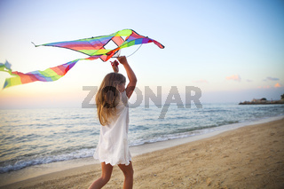 Little girl with flying kite on tropical beach at sunset