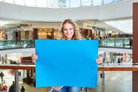 Teenager hält ein blaues leeres Schild