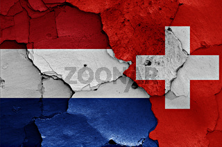 flags of Netherlands and Switzerland painted on cracked wall