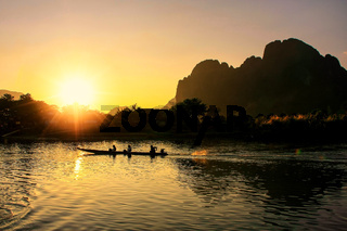 Sunset over Nam Song River with silhouetted rock formations and a boat in Vang Vieng, Laos