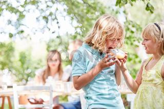 Junge beißt hungrig in ein Stück Kuchen
