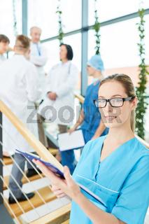 Frau als Assistentin vor ihrem Chirurgie Team