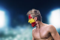 Football fan with spain flag painted on his face in front of night stadium