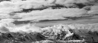 Black and white panoramic view on snow mountains and sunlight cloudy sky at winter evening