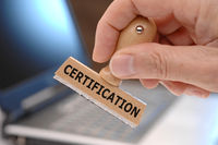 certification printed on rubber stamp in hand