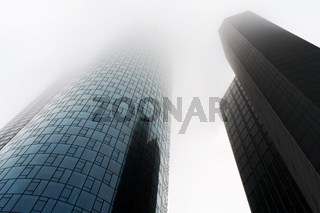 low angle view of two skyscrapers shrouded in fog or mist in the banking district of Frankfurt Germany