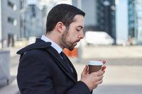 Business Mann trinkt einen Becher Kaffee
