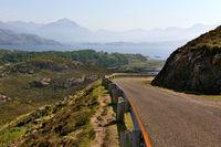 Einspurige Straße in den Bergen mit See im Hintergrund