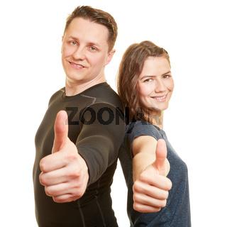 Zwei Fitnesstrainer halten Daumen hoch