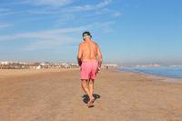 Shirless senior man in shorts walking on sandy beach.