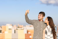 Young man and woman making selfie otdoors
