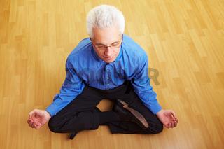 Mann meditiert im Wohnzimmer