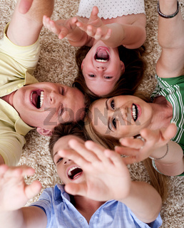 Happy family of four lying on the carpet and having gala time