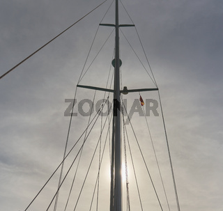 Mast of the sailing yacht against cloudy sky at sunset