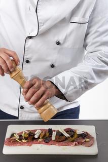 Koch bereitet eine Fleischroulade zu