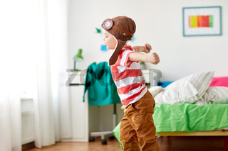happy little boy in pilot hat playing at home