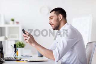 businessman with smartphone and notebook at office