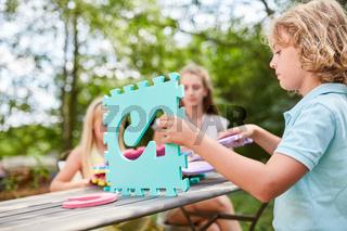 Kinder bauen aus Puzzleteilen ein Haus