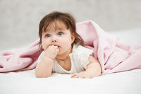 Portrait of baby girl lying on blanket at home