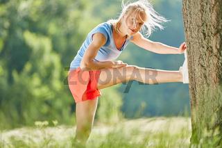 Junge Frau macht zum Aufwärmen Stretching