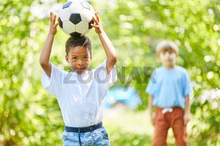 Afrikanischer Junge balanciert mit Fußball