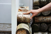 The worker restores a window in the historical building - a birch house of the Gatchina park, fastening pieces of birch with a screwdriver.
