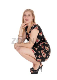 Beautiful young woman in a dress crouching