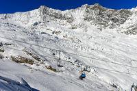 Skifahrer auf einem Sessellift vor dem Feegletscher und den Mischabelhörner Täschhorn und Dom
