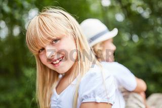 Niedliches blondes Mädchen sitzt lächelnd
