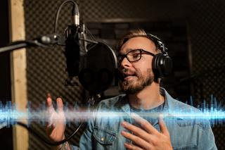 man with headphones singing at recording studio