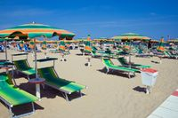 chaise longue and umbrellas on a sandy beach in Rimini