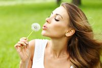 Woman blows dandelion
