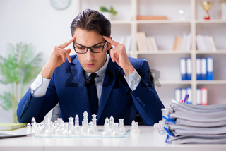 Young businessman playing glass chess in office