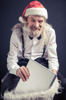 Old wrinkled man in Santa hat holding holding laptop.