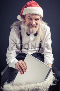 Old wrinkled man in Santa hat holding holding laptop.