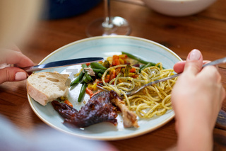 hands of woman eating pasta and roast chicken