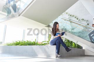Studentin liest Buch und lernt für Prüfung