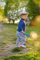 Toddler child outdoors. Rural scene with one year old baby boy wearing flat cap