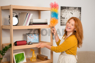 Woman smiling while wiping dust on wooden shelves.