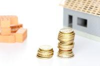 Hausbau mit Geld und Ziegelsteinen