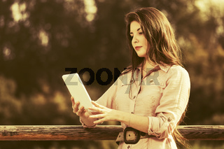 Young fashion woman using tablet computer outdoor