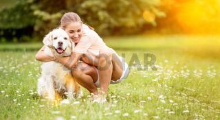 Frau umarmt Golden Retriever Hund im Garten