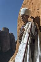 Koptischer Priester  hoch oben an einer steilen Felswand am Eingang zur Felsenkirche Abuna Yemata