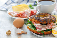 Plate with bagel with arugula, bacon and egg.