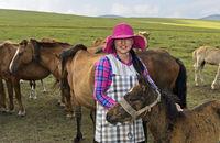 Junge mongolische Frau mit modischem Hut zwischen Pferden, Mongolei