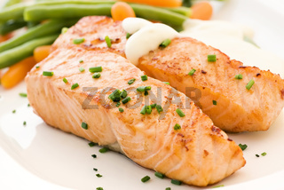 Salmon filet with beans and carrots as closeup on a white plate