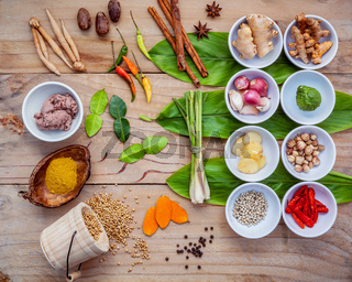 Various of thai food cooking ingredients for spice red curry paste ingredient of thai popular food on galanga leaf background. Spices ingredients chili ,pepper, nutmeg, garlic and Kaffir lime leaves.